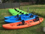 Green Single Kayaks, Blue Fishing Kayaks And Double Orange Kayak Sitting On A Row On Green Grass