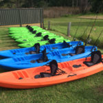 Green Single Kayaks, Blue Fishing Kayaks And Double Orange Kayak Sitting On A Row On Green Grass