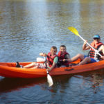 Father And Two Sons With Life Jackets On Seated In Orange Kayak On The Water