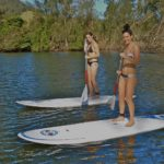 Smiling Women Standing On Paddle Boards On Water