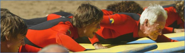 Smiling people learn to surf in matching wetsuits laying down side by side on surfboards on the sand