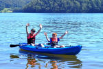 Smiling Mother And Son Waving With Life Jackets On In Blue Kayak On The Water