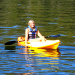 Girl Smiling With Life Jacket On In Yellow Kayak On The Water