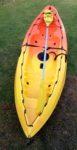 Kayak Hire Orange And Yellow Kayak On The Grass