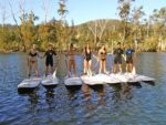 Smiling Hen's Party Group Posing And Standing On Paddle Boards With Bushy Background