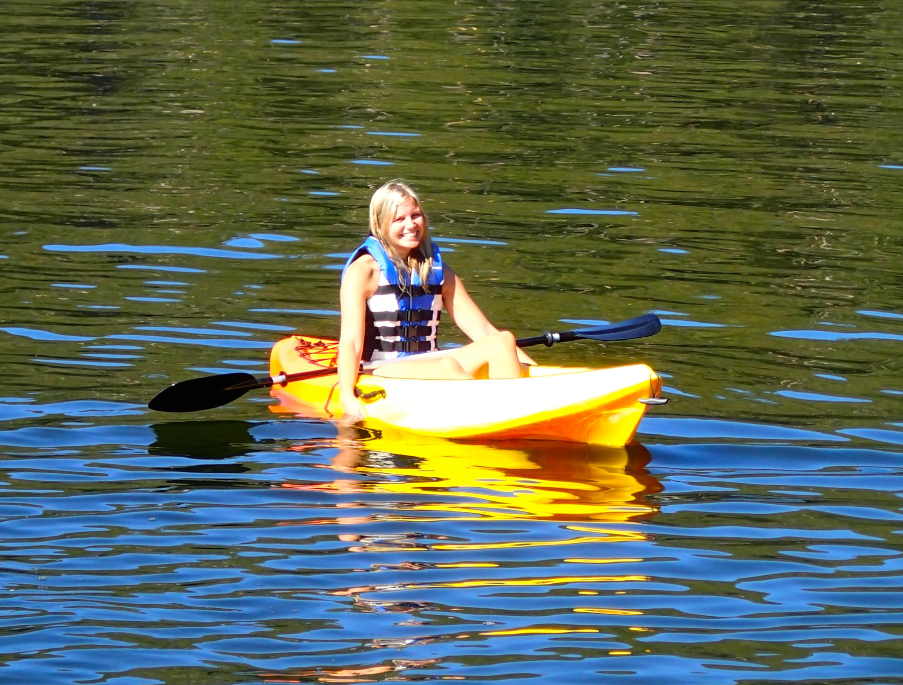 Smiling Girl With Life Jacket On Seated In Kayak On The Water