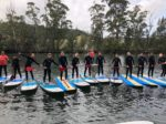 Group Posing For Photo Standing On Paddle Boards With Paddles In Their Hands On The Water