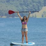 Women Standing On Paddle Board On The Water Holding Paddle With Both Hands Above Her Head