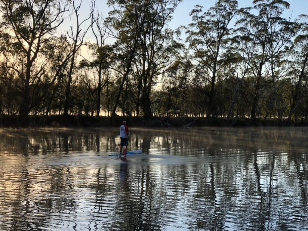 Water reflecting dusk lit sky and tree lined bank and man standing on paddle board in water