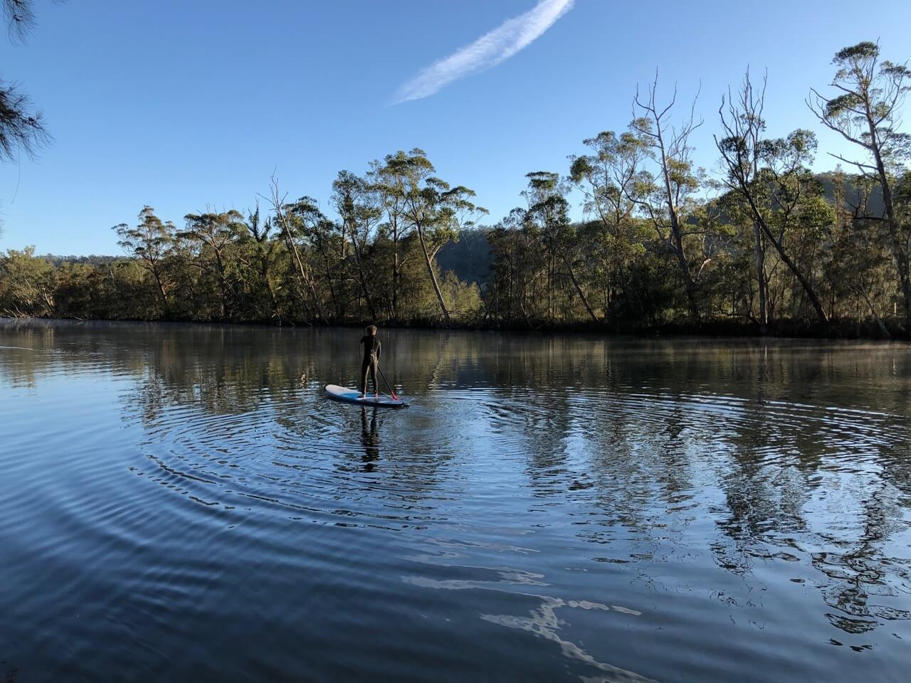 Man standing on paddle board on water reflecting the sky and tree lined bank