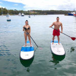 Smiling Couple Standing On Individual Paddle Boards On The Water With Boats In The Back Ground