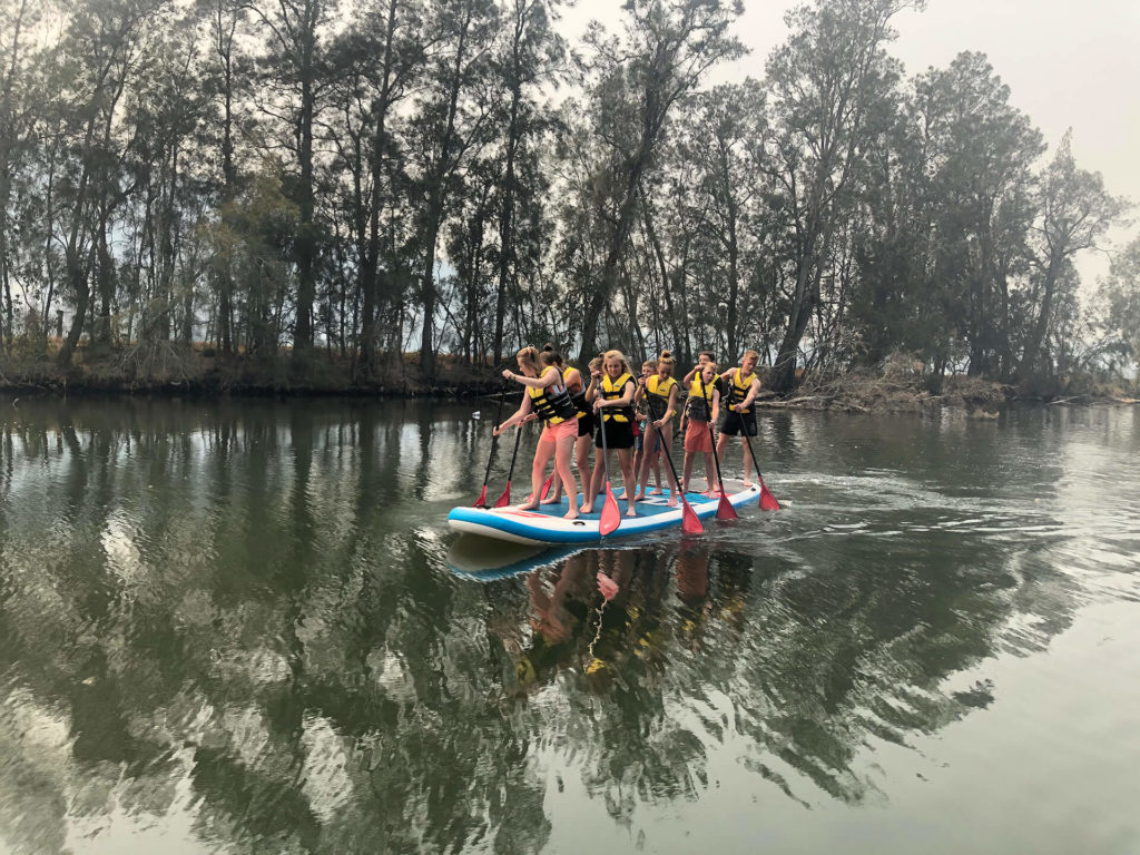 Group of women paddling on monster stand up paddle board on the water with trees lining the bank in the background